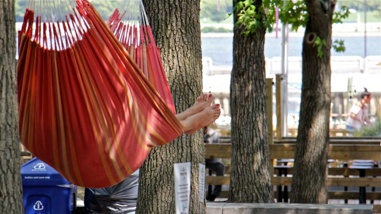 A woman finds relief from the heat in a hammock in the shade by the river at Spruce Street Harbor Park. (Emma Lee/WHYY)