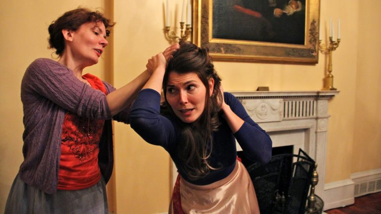 Jennifer Summerfield (left), as Hedda, and Jessica DalCanton as Thea rehearse a fight scene from Hedda Gabler in the historic Physick House in Philadelphia. (Emma Lee/WHYY)