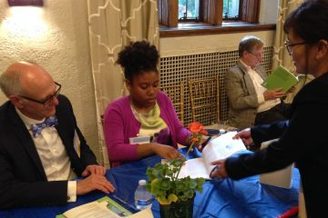 James Buehler (left) of Drexel  and a student journalist from St. Martin de Porres school sign books. (J. Woods/WHYY)