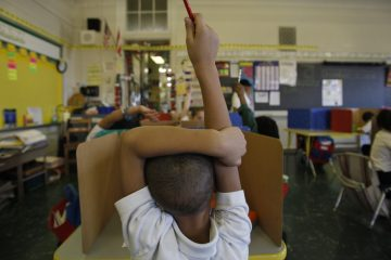 A student raises his hand at Isaac Sheppard School in Philadelphia. (Photograph by Jessica Kourkounis)