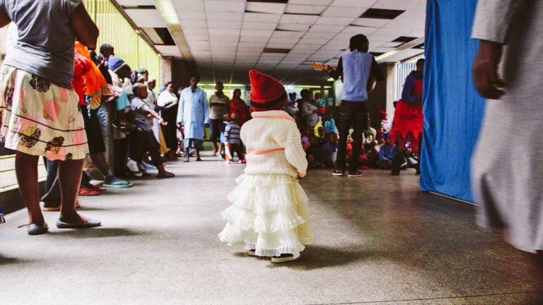 A small patient at a cancer ward in Kenya watches as clowns perform a sketch. (Brenna Daldorph/for WHYY)