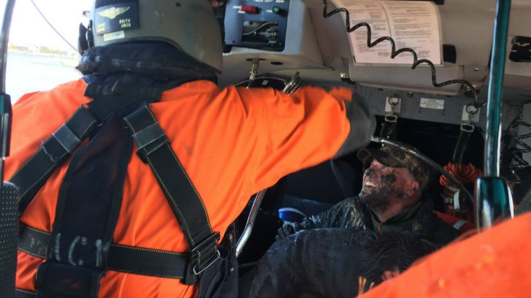 A muddy hunter smiles inside a Coast Guard helicopter after being rescued with his dog. (photo courtesy U.S. Coast Guard/ Petty Officer 1st Class Seth Johnson)