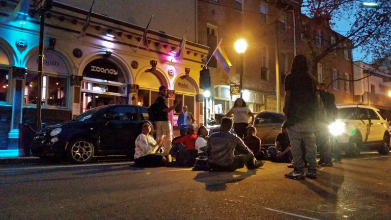 A small group protests racism in the Gayborhood by shutting down the street in front of ICandy. (Peter Crimmins/WHYY)