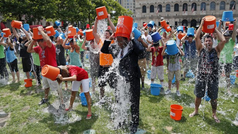 Some 200 people participate in the Ice Bucket Challenge at Boston's Copley Square to raise funds and awareness for ALS. The idea is easy: Record yourself dumping a bucket of ice water over your head, post it on social media, then challenge friends to do the same within 24 hours or pay up for charity. (AP Photo/Elise Amendola)