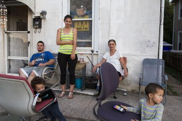 """From left to right: Anthony Petraline, 22, Crystel Petraline, 27, Mary Petraline,52, with Mason, 4, and Liam, 3, in front of their home near one of the boundaries for the 7th and the 13th districts in Norristown, Pennsylvania. Crystel and Mary said they plan on voting for Hillary Clinton. """"Her being about children will definitely benefit us,"""" said Crystel. (Lindsay Lazarski/WHYY)"""