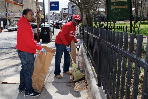 Volunteers from Kappa Alpha Psi fraternity cleared leaves and trash in front of Germantown's Vernon Park during 2013 Clean-Up Day efforts. (Jana Shea/for NewsWorks )