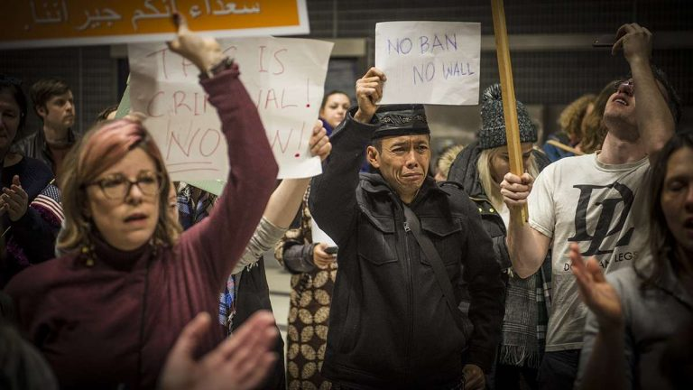 Protesters angered by President Donald Trump's 2017 executive order that prevented refugees, visa and green card holders from entering the U.S. rally at Philadelphia International Airport. (Branden Eastwood/for WHYY)