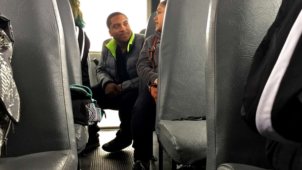 Hakeem Thompson, a Kensington Health Sciences Academy senior, chats with other students during a bus ride to Methacton.