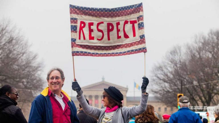 Laura Reisman-Dennis holds up a sign during the Women's March in Philadelphia Saturday morning. (Brad Larrison for WHYY)
