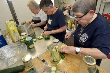 Emilia Weksel, Velma Supperer and Janet Stechman prepare pickle jars at the Salvation Army Roxborough Corps Community Center. (Bas Slabbers/for NewsWorks)