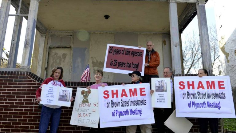 East Falls residents protest outside of a blighted property on Conrad Street. (Bas Slabbers/for NewsWorks)