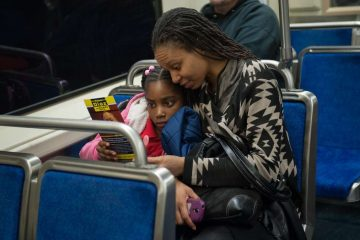 Estelle Charles and her daughter J'adore Dorvil, 8, of West Philadelphia, read a flyer that Nelson Diaz had just given them on the subway. (Tracie Van Auken/for NewsWorks)