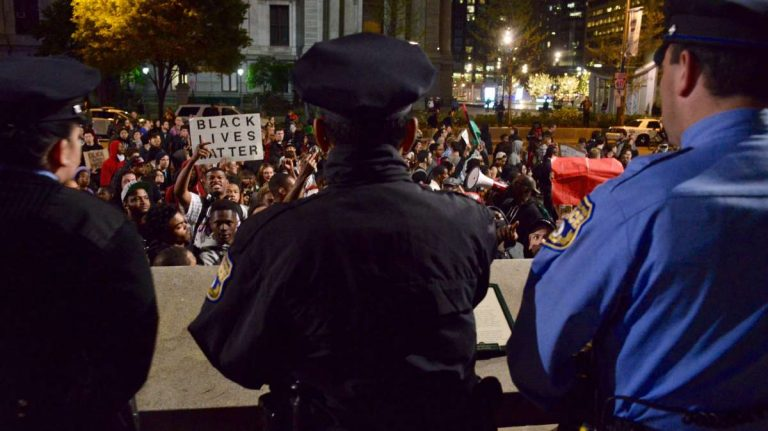 Police officers watch as protesters pass by and briefly stop across Philadelphia's City Hall Thursday night. (Bastiaan Slabbers/for NewsWorks)