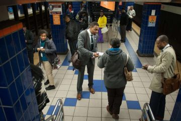 Mayoral candidate Doug Oliver (center) hands out flyers to Broad Street Line passengers at the Olney station. He has been campaigning on SEPTA trains and buses since January. (Tracie Van Auken/for NewsWorks)