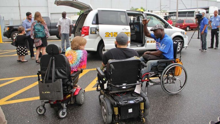 Accessibility activists gather round as Philadelphia introduces new wheelchair accessible taxis. (Emma Lee/WHYY)