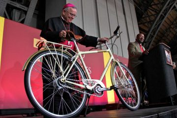 At the opening ceremony of the World Meeting of Families Tuesday, Mayor Michael Nutter presents the city's gift for Pope Francis -- a bicycle, received on the pope's behalf by Archbishop Charles Chaput. (Emma Lee/WHYY)
