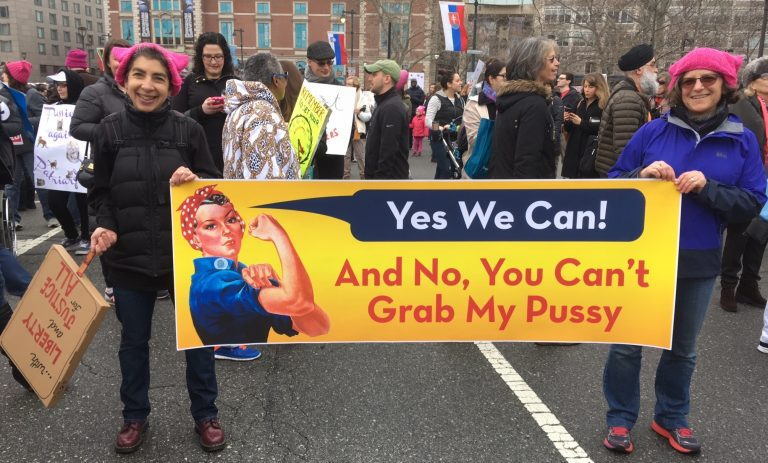 The author (left) is shown holding a sign with her partner Elissa Goldberg. (Image courtesy of Anndee Hochman)