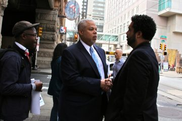 Mayoral candidate Tony Williams talks to campaign spokesman Al Butler outside the Reading Terminal Market on Tuesday. (Emma Lee/WHYY)