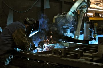 A human welder works beside a robot welder at PTR Baler in Port Richmond. (Emma Lee/WHYY)