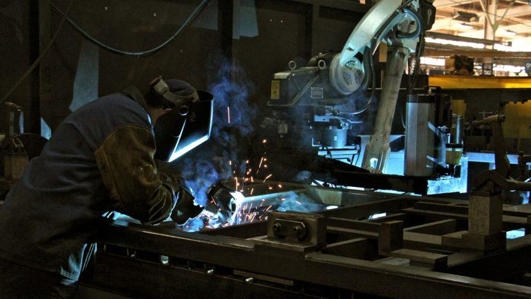 A human welder works beside a robot welder at PTR Baler in Port Richmond. (Emma Lee/WHYY)