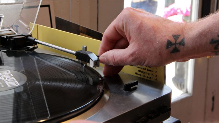 Isaac Williams puts a record on at AKA Music in Old City. (Emma Lee/WHYY)