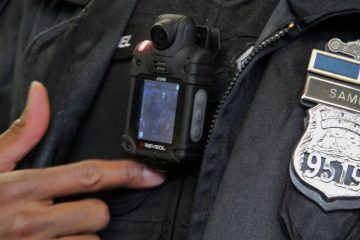 Officer James Samuel turns on a body camera with a small video display. (Emma Lee/WHYY)