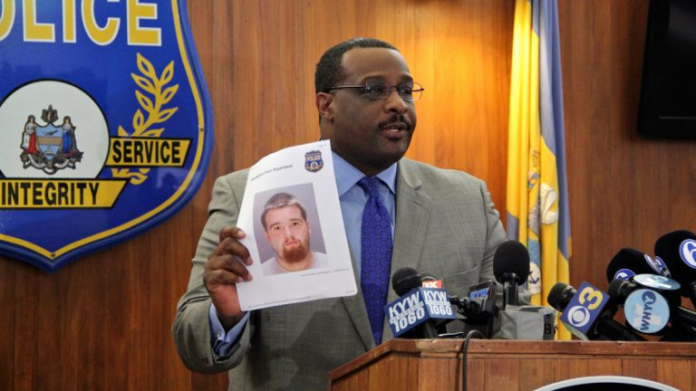 Philadelphia Homicide Unit Capt. James B. Clark Jr. holds a photo of Pedro Redding, charged with murder in the shooting death of Kiesha Jenkins. Clark said other suspects were involved and Redding was not the triggerman. (Emma Lee/WHYY)
