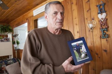 Joe Rosipal, 70, a retired Monroeville police officer, with a photograph of himself in his 40s, when he was part of the motorcycle division. (Irina Zhorov/WESA)