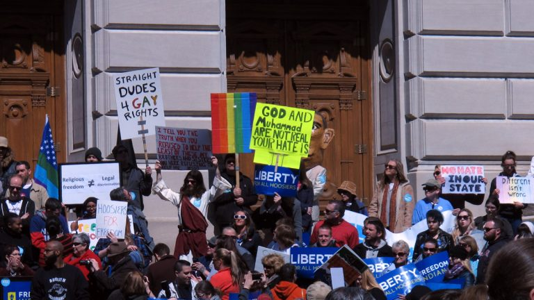 Some of the hundreds of people protesting against 'religious freedom' legislation signed last week by Gov. Mike Pence are shown standing on the Indiana Statehouse's south steps on March 28. (AP Photo/Rick Callahan)