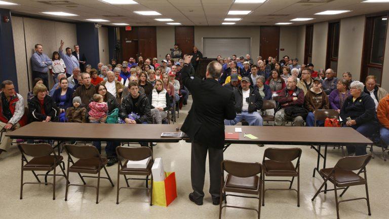 Precinct chair John Anderson, center, directs voters before a Republican party caucus in Nevada, Iowa, Monday, Feb. 1, 2016. (AP Photo/Patrick Semansky)