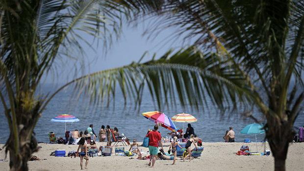 Early arrivals relax on the beach Thursday