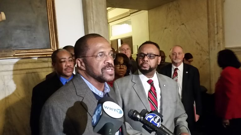 Philadelphia Sheriff Jewell Williams, at podium, talks about scammers saying they represent his office. Councilman Curtis Jones, right, says his constituents have gotten some of the bogus calls. (Tom MacDonald/WHYY)