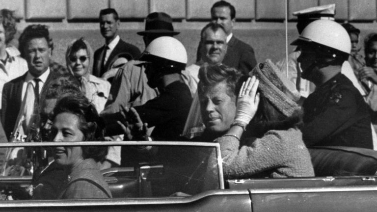 President John F. Kennedy is seen riding in a motorcade approximately one minute before he was shot in Dallas, Tx., on Nov. 22, 1963. In the car riding with Kennedy are Mrs. Jacqueline Kennedy, right, Nellie Connally, left, and her husband, Gov. John Connally of Texas. (AP Photo)
