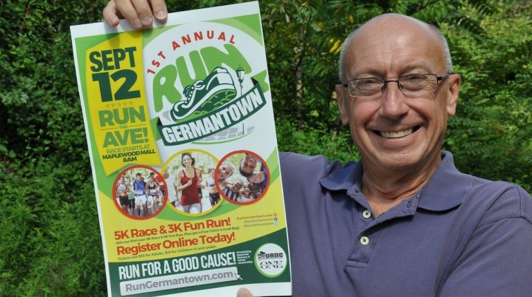 Joe Waldo holds up a poster for Run Germantown. (Greta Iverson/for NewsWorks)