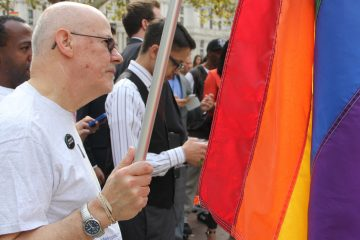 John Speer of Philadelphia carries a rainbow flag to Love Park in Philadelphia on Thursday for an announcement from state reps. Brian Sims and Steve McCarter about the introduction of a same-sex marriage bill in Pa. (Emma Lee/for NewsWorks)