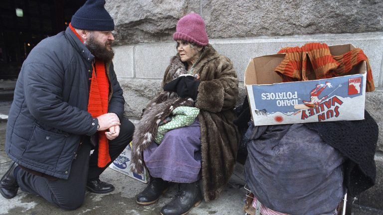 A man stops to talk to a homeless woman outside of Reading Terminal Market in Philadelphia.  (AP Photo/Charles Krupa, file)