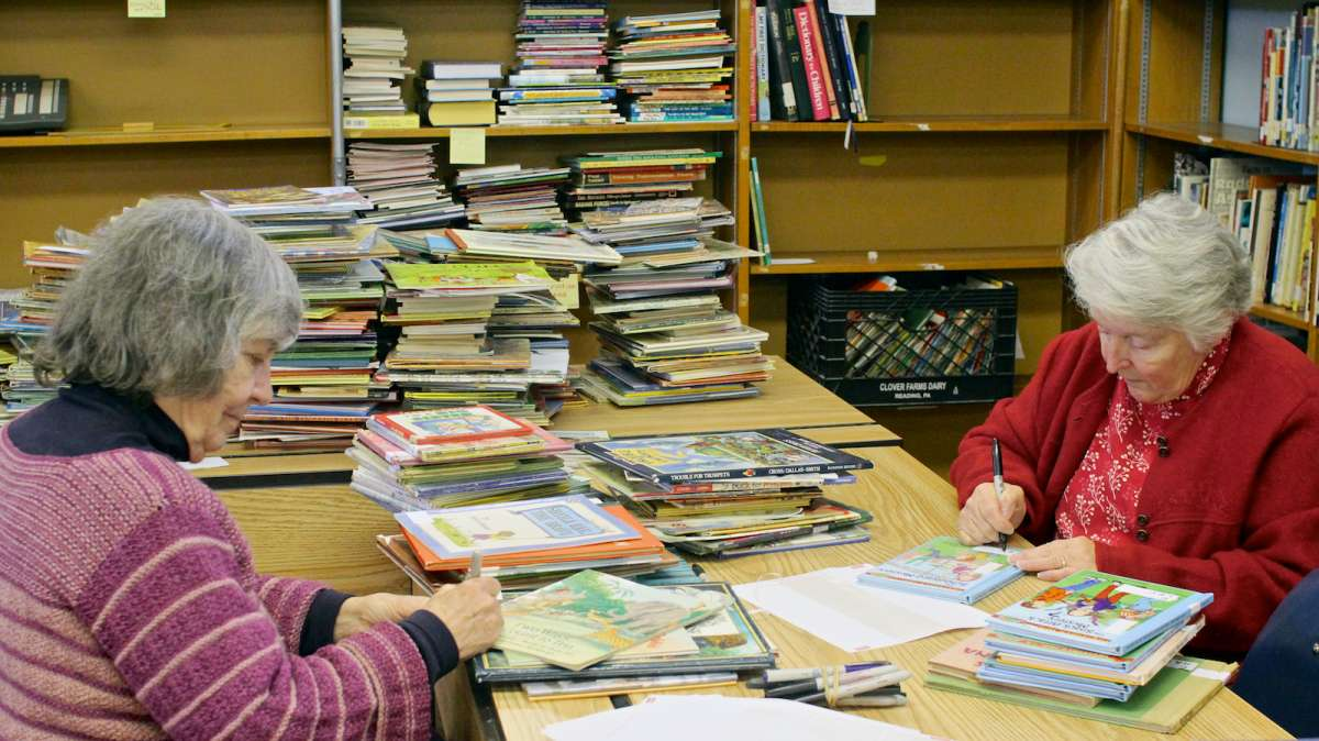 Neighborhood volunteers from Mutual Mt. Airy and the local town watch help sort, classify and label incoming book donations. (Jana Shea/for NewsWorks)