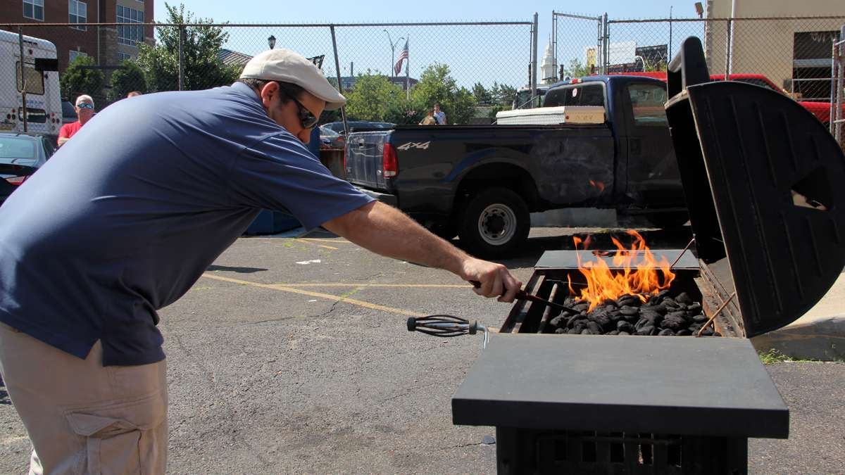 Sean Sullivan of Local 22 demonstrates the danger of using too much lighter fluid. (Emma Lee/WHYY)