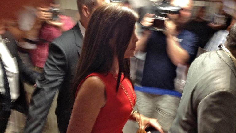 Pennsylvania Attorney General Kathleen Kane rushes through a media gauntlet on her way to court in Norristown, where she was ordered to stand trial on charges of leaking grand jury material. (Dave Davies/WHYY)