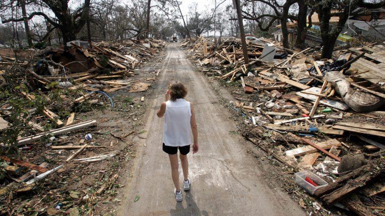 Rhonda Braden walks through the destruction in her childhood neighborhood