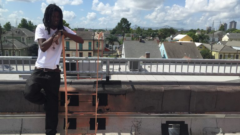 Kendall Hooker stands on the roof of the New Orleans Healing Center in the city's Marigny neighborhood. Behind him is the edge of the skyline
