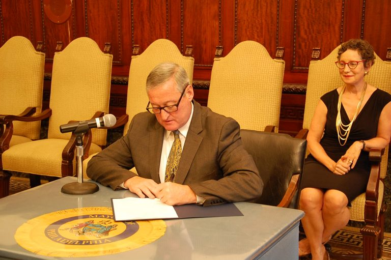 Mayor Kenney signs the executive order as Liz Hersh