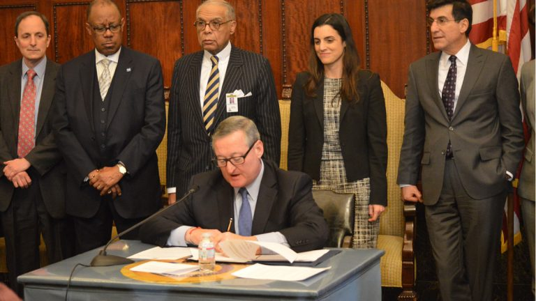 Philadelphia Mayor Jim Kenney signs several executive orders yesterday just hours after taking the oath of office. (Tom MacDonald/WHYY)
