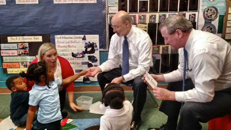 Four- and 5-year-olds in Erin Dowling's preschool class at the West Philadelphia Community Center play a game with Gov. Tom Wolf and Mayor Jim Kenney. (Katie Colaneri/WHYY)