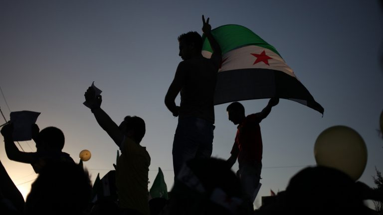Syrian protesters wave the Syrian revolutionary flag during a protest in front of the Syrian embassy in Amman, Jordan, Friday, Aug. 23, 2013.  Anti-government activists accused the Syrian regime of carrying out a toxic gas attack that is thought to have killed at least 100 people, including many children. (AP Photo/Mohammad Hannon)
