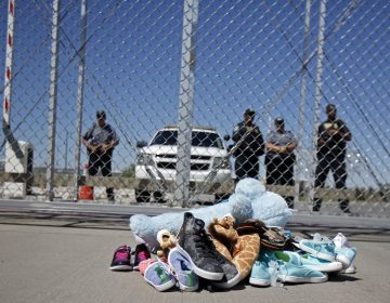 Shoes and a teddy bear, brought by a group of U.S. mayors, are piled up outside a holding facility for immigrant children in Tornillo, Texas, near the Mexican border, Thursday, June 21, 2018.  Mayors from more than a dozen U.S. cities including New York and Los Angeles gathered near the holding facility to call for the immediate reunification of immigrant children with their families (Andres Leighton/AP Photo)