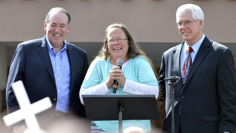 Rowan County Clerk Kim Davis, center with Republican presidential candidate Mike Huckabee, left, and attorney Mat Staver, right, founder of the Liberty Counsel, the Christian law firm representing Davis, at her side, greets the crowd after being released from the Carter County Detention Center, Tuesday, Sept. 8, 2015, in Grayson, Ky. (AP Photo/Timothy D. Easley)