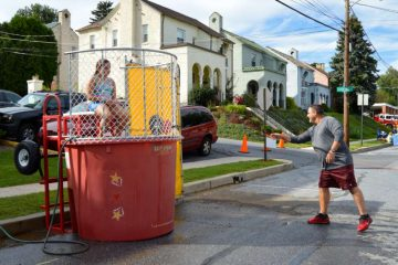 Mount Penn resident Jeff Motes lobbed a ball at the dunk tank target (and subsequently soaked his niece). He says a consolidation between Mount Penn and Lower Alsace would be 'great for the kids. The borders are so close, sharing resources would be a good thing.' (Kate Lao Shaffner/WPSU)