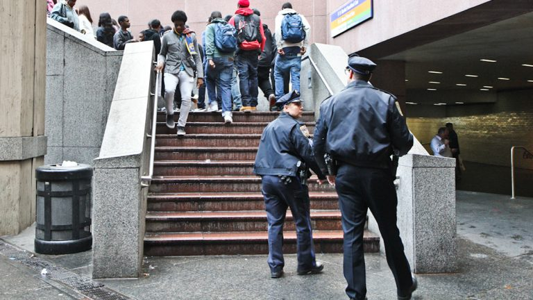 SEPTA Police watch Philadelphia students as they exit a subway concourse in Center City. (Kimberly Paynter/WHYY)