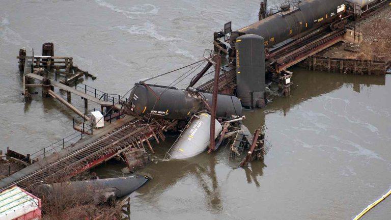 Derailed freight train cars lay in water in Paulsboro, N.J., Friday, Nov. 30, 2012. (AP Photo/Cliff Owen)